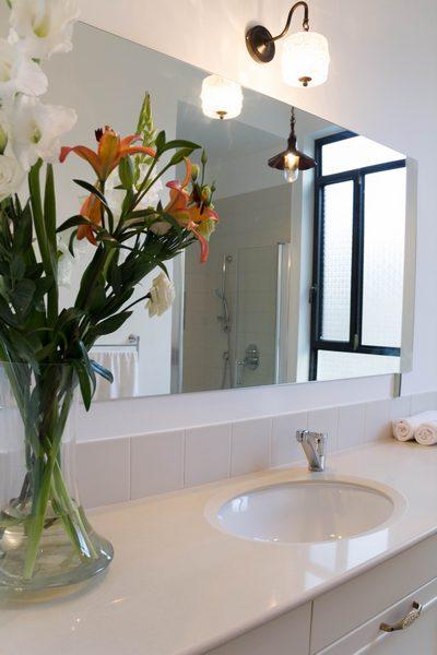 המראה הגדולה מייצרת השתקפות של החלון ושל המקלחון הנמצא ממול לאסלה